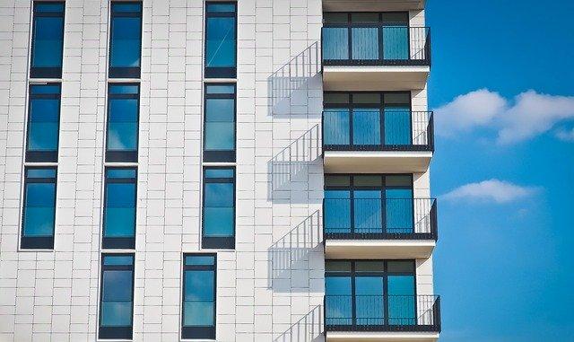 Svetlá budova s veľkými presklenými dverami, oknami a balkónmi s tmavým zábradlím.jpg