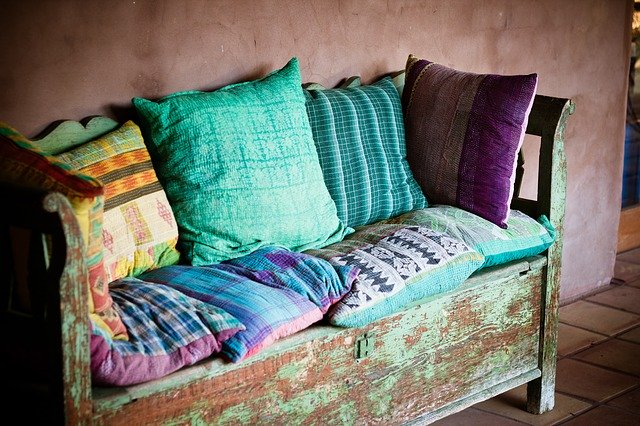 Drevená lavica s farebnými vankúšmi a dekami.jpg