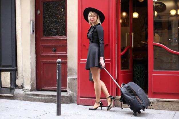 leggy-blonde-short-black-dress-with-hat-suitcase-is-walking-down-street-paris_153325-154