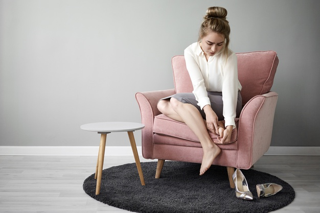 portrait-tired-exhausted-young-female-office-worker-formal-wear-sitting-armchair-massaging-her-foot-relieve-pain-because-wearing-high-heeled-shoes-all-day-health-wellness_343059-4170